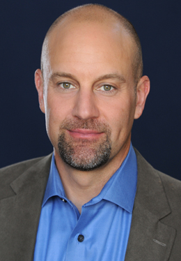 small-res crop - Mike headshot - blue shirt, brown jacket